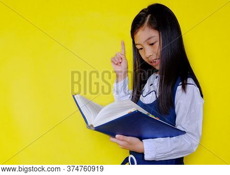 A Cute Young Asian Girl In White And Blue School Uniform Holding A Textbook, Reading And Trying To S