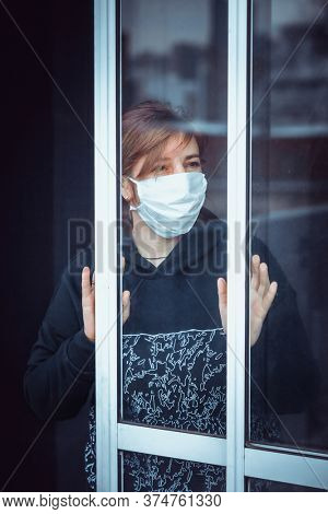 woman near the window during a pandemic
