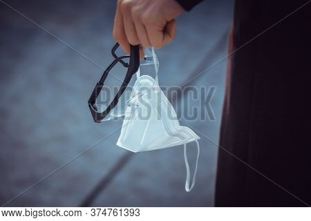 protective mask and glasses in hand