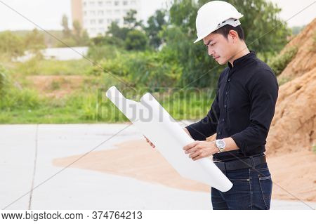 Young Engineer Surveying Land To Construction House Using Blueprint To Plan The Work.