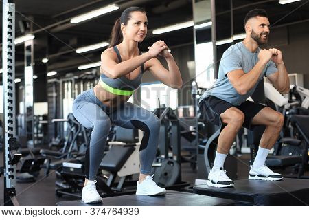 Fit Couple Doing Jumping Squats In Crossfit Gym.
