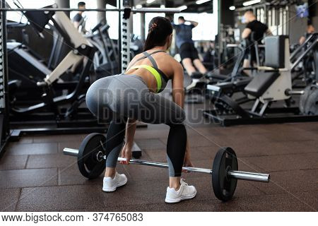 Full Length Portrait Of Young Woman Lifting Barbell In Gym.