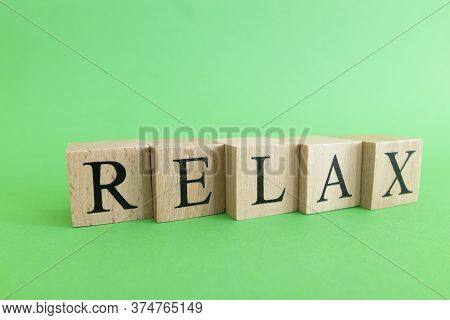 The Word Relax Made From Wooden Cubes. Rest And Calm Concept.