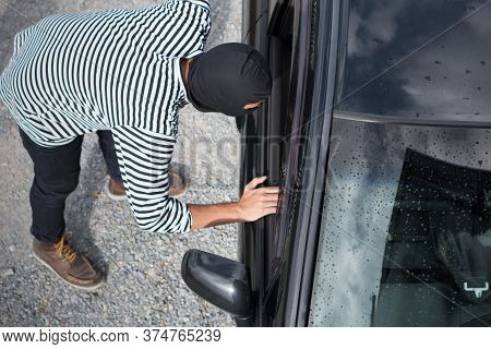 Thief In The Black Mask Looking In The Car And Trying To Break A Car Window To Steal A Car.