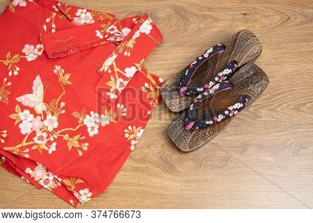 Japanese Traditional Geta Sandal And Traditional Clothes Of Kimono, Yukata On Wooden Floor.