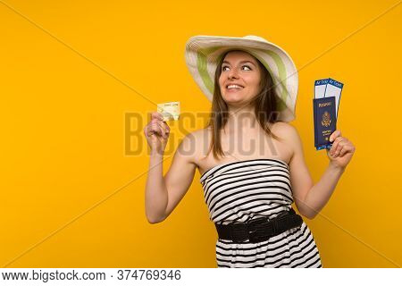 Joyful Young Woman In A Straw Hat And A Striped Dress Is Holding Airline Tickets With A Passport And