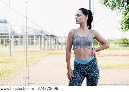 Young Woman Rests After Jogging. Caucasian Female Fitness Model Working Out In The Morning. Fit Youn