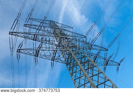 High Voltage Mast In Front Of Blue Sky With White Clouds