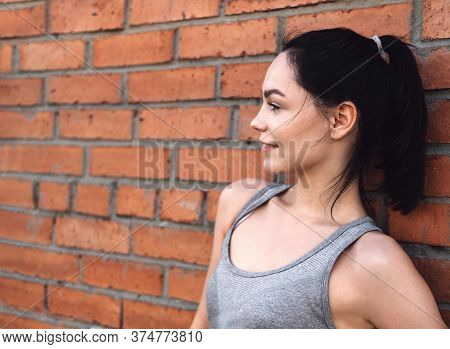 Close-up Portrait Of A Smiling Woman. Young Woman Rests After Jogging Against A Red Brick Wall. Cauc
