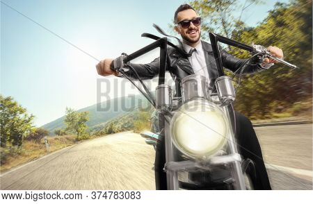 Man riding a chopper motorbike on an open road in a picturesque area