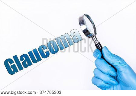 Glaucoma Text Written On The Background Of A Magnifying Glass In The Doctor Hand In A Medical Glove.