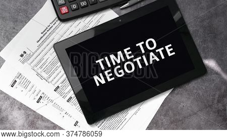 Time To Negotiate On A Black Tablet And With Tax Forms And Calculator