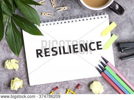 Resilience On A Notebook With A Cup Of Coffee, Compressed Sheets, Crayons, Stapler