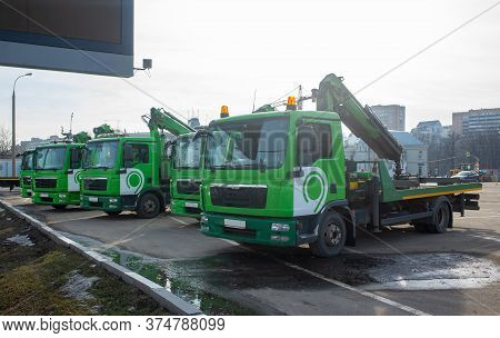 Green Tow Truck Service For Paid City Parking In A Car Park On A Clear Day.