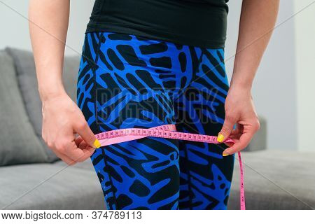 Slimming Woman Measuring Her Body At Home. Sporty Girl Measuring Her Leg With A Metric Tape Measure,