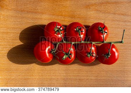 Branch With A Group Of Red Tomatoes Lies On An Oak Board. Summer Season. Web Banner.