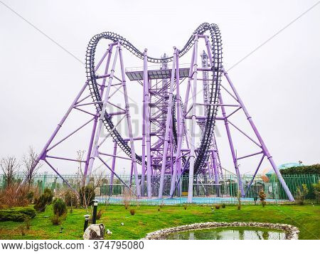 Russia, Sochi 14.03.2020. Large Lilac Amusement Ride Roller Coaster On The Plain Fenced By A Blue Me