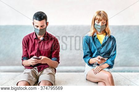 Bored Addicted Couple With Protective Masks Using Tracking App With Mobile Smartphones - Young Mille