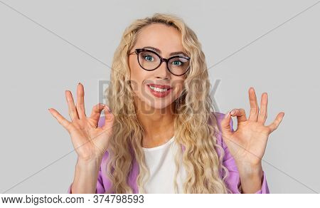 Portrait Of A Satisfied Positive And Charismatic Happy Woman In Glasses, Showing Ok Signs And Smilin