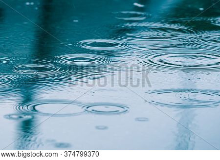 Rain Drops On The Surface Of The Water Forming Ripples