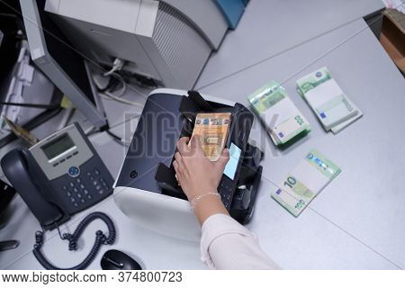 Bank employees using money counting machine while sorting and counting paper banknotes inside bank vault. Large amounts of money in the bank