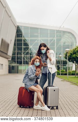 Two Young Women In Protective Masks Stand Near The Airport And Look For A Location On A Mobile Phone