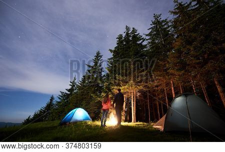 Rear View Of A Couple In Love Holding Hands Standing By The Fire Between Tents On The Background Of