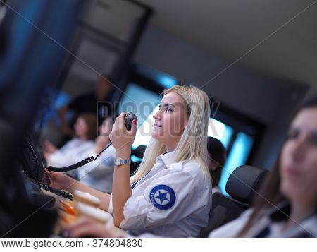 group of female security operators working in a data system control room  Technical Operators Working at  workstation with multiple displays, security guards working on multiple monitors in surveillan