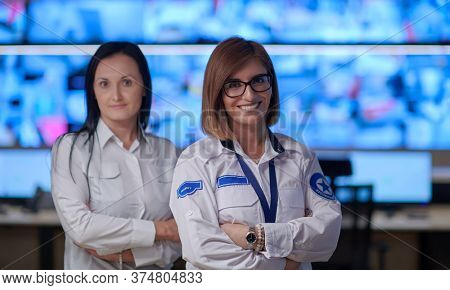group portrait of female security operator while working in a data system control room offices Technical Operator Working at  workstation with multiple displays, security guard working on multiple mon