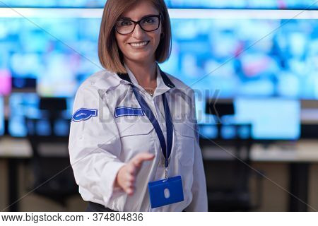 Female security operator extending a hand for a handshake while working in a data system control room offices Technical Operator Working at  workstation with multiple displays, security guard working
