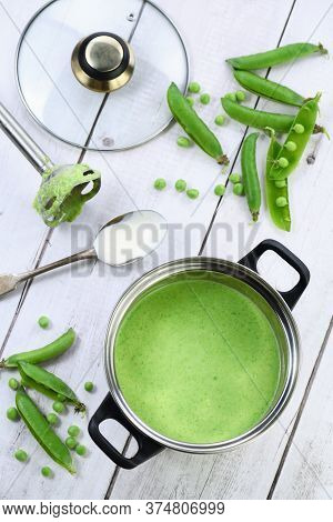 Saucepan Of Freshly Cooked Soup Of Mashed Green Peas And Cream On The Table.