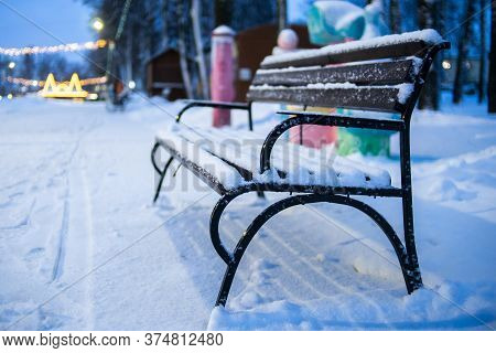 Empty Bench In Winter In The Evening Park. Snow Bench Without People