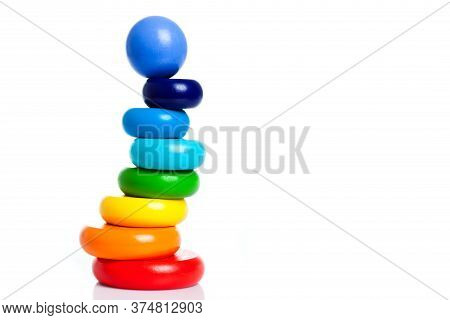 Child Pyramid Of Round Shape From Wooden Parts Of Different Colors Isolated On White Background With