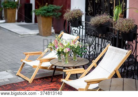 A Chaise Lounge On The City Street At The Building Of The Hotel Is A Wooden Lounger With A Round Tab