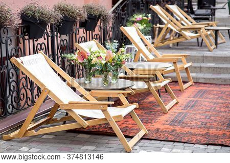 A Wooden Chaise Lounge With Textiles In The Street Is On The Sidewalk Of A Tile With A Carpet, An Ou