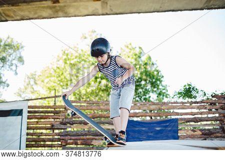 Skater Boy Rides On Skateboard At Skate Park Ramp. Kid Practising Skateboarding Outdoors On Skatepar
