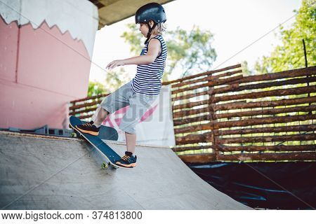 Child Skateboarder During Learning Tricks On A Ramp In An Urban Skate Park. Boy In A Sports Helmet R