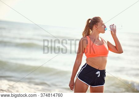 young caucasian blonde female drinking water from bottle on a beach, making pause from exercising
