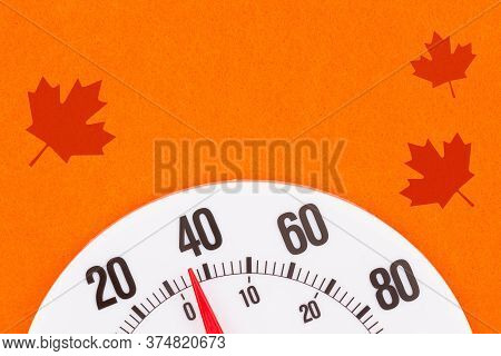 Closeup Of A Thermometer At 40 Degrees With Leaves With A Bright Orange Background And With Copy Spa