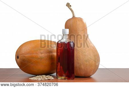 Pumpkins, Pumpkin Oil In A Bottle And Pumpkin Seeds On A Table. Isolated On White Background.