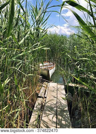 Boat Moored To Wooden Walkways In The Reeds On Lake Balaton In Hungary.