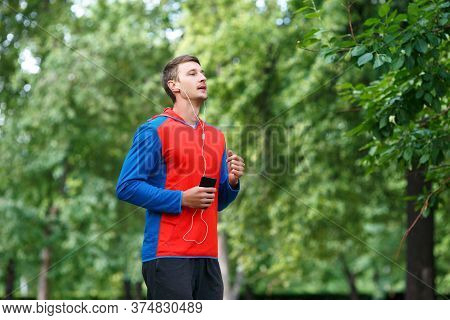 Male Jogger Is Training In The Park And Listening To The Music. Morning Running.