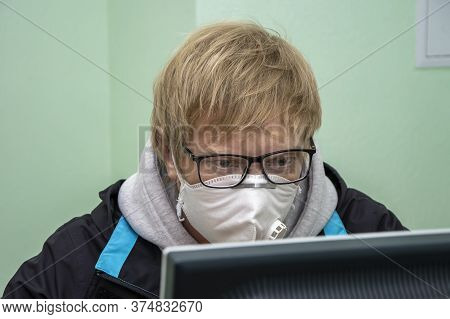 A Fair-haired Young Man With Glasses And A Medical Mask Works At A Computer, Looks Like A Nerd, Work