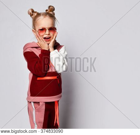 Worried Or Frightened Little Girl In Stylish Jogging Suit And Sunglasses Touching Chicks With Hands.
