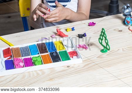 Children's Table. On It Is A Set Of Plasticine. A Girl With Painted Nails Sculpts A Craft