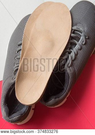 Orthopedic Insoles And Sports Shoes On Red - White Background. Prevention Of Orthopedic Foot Disease