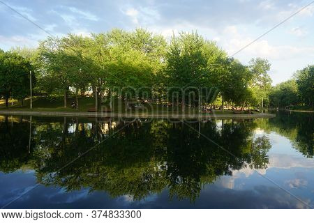 Montreal, Qc / Canada - 7/3/2020: Reflections Of Trees On Ake Water, La Fontaine Park.