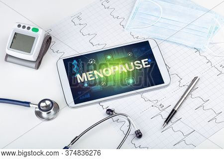 Tablet pc and medical stuff with MENOPAUSE inscription, prevention concept