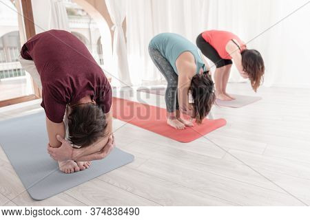 Group Of People Practicing Yoga. Uttanasana Position With Elbow Grab. Intense Stretch Pose, Forward