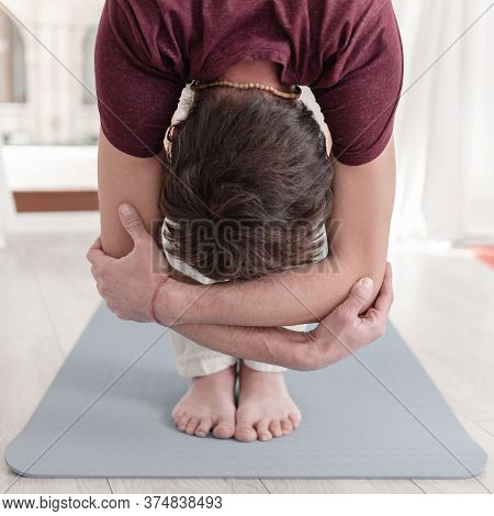 Man In Uttanasana With Elbow Grab. Intense Stretch Pose, Forward Bend, Head To Knees. Seguence Of Su